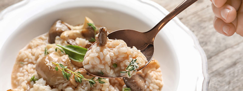 Person about to eat mushroom risotto using a spoon
