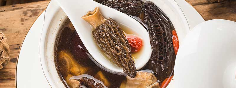 A piece of cooked morel mushroom being scooped out of a stew using a ceramic spoon